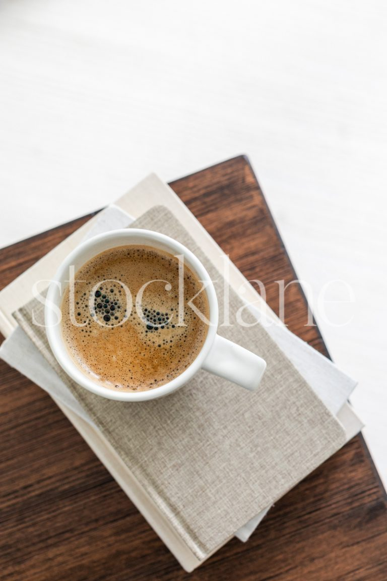 Vertical stock photo of a cup of coffee on a stack of neutral colored books.