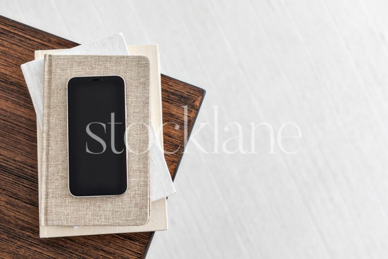 Horizontal stock photo of a phone on a stack of neutral colored books.