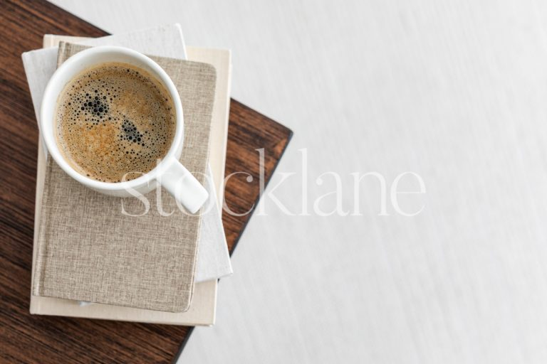 Horizontal stock photo of a coffee cup on a stack of neutral colored books.
