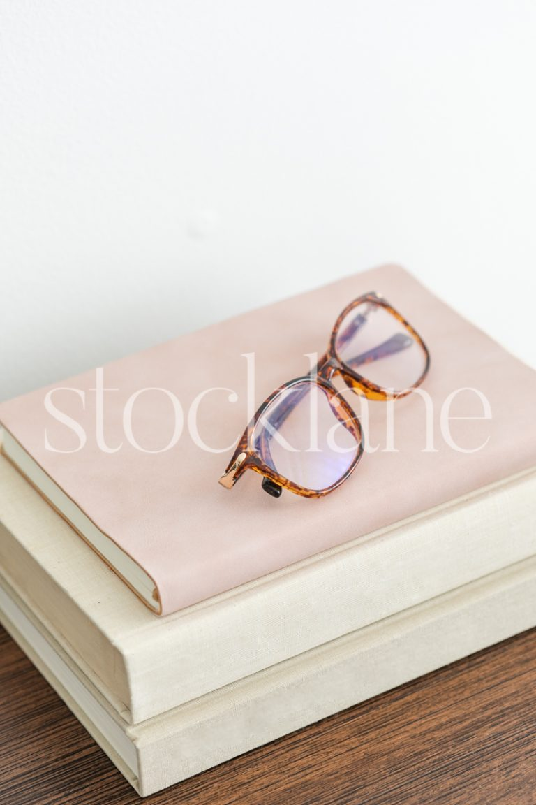 Vertical stock photo of glasses on a stack of books.