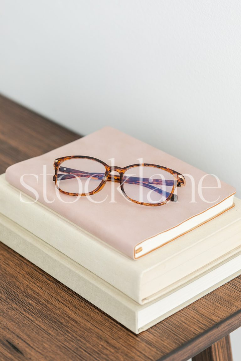 Vertical stock photo of books on a table with a pair of glasses