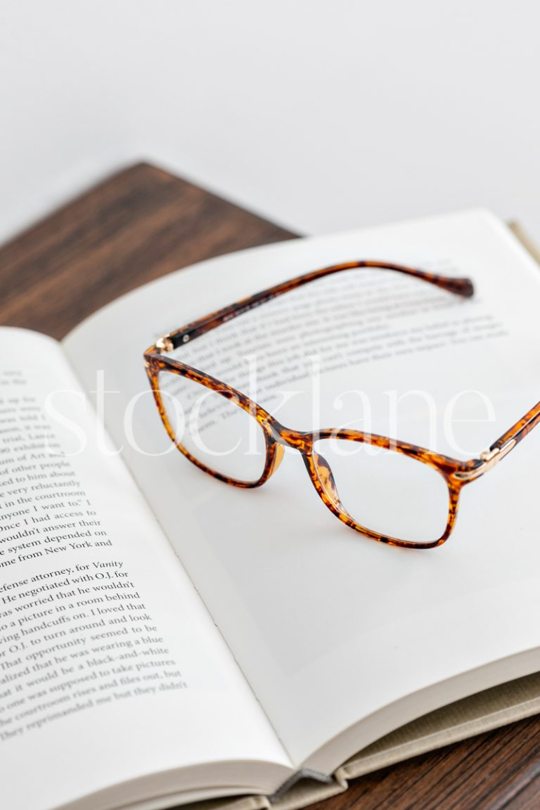 Vertical stock photo of a book and glasses on a table