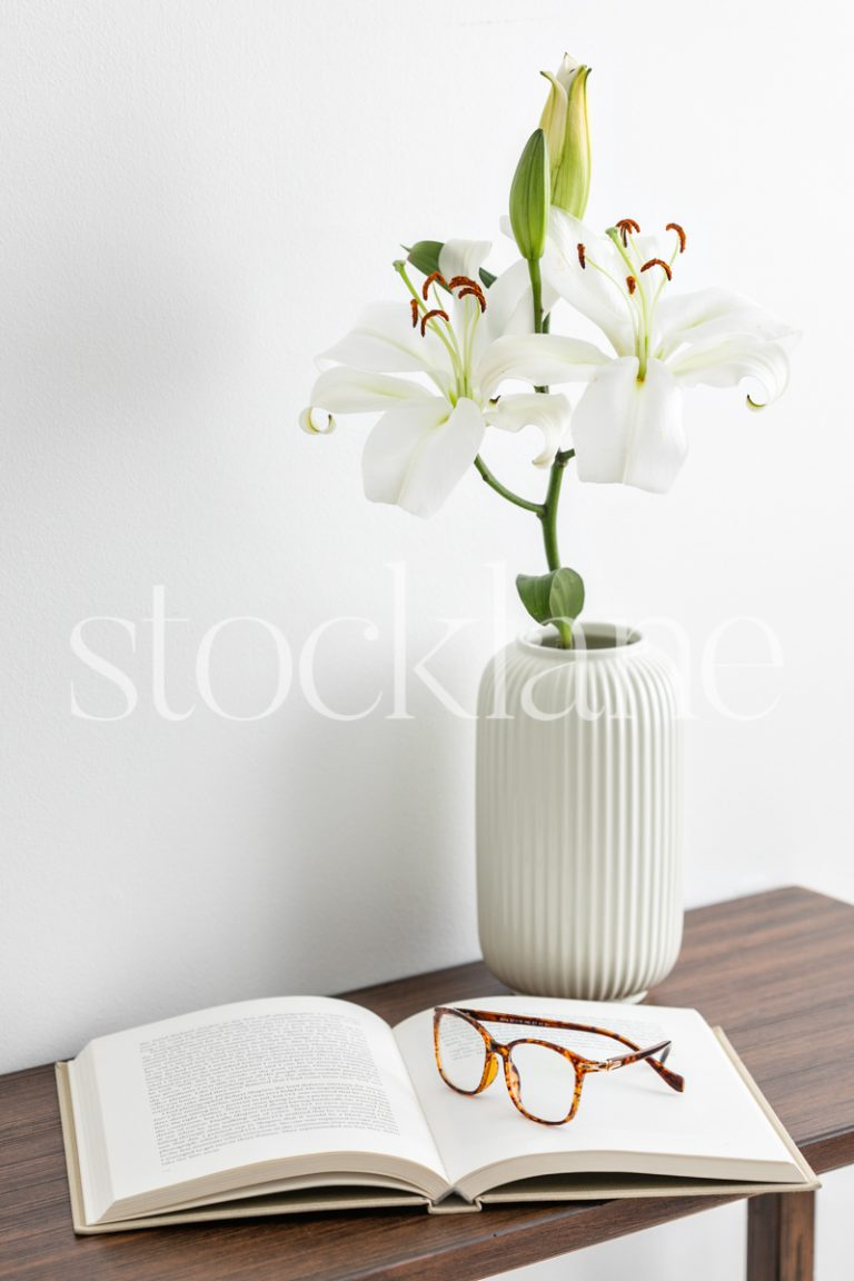 Vertical stock photo of white asian lilies with a book and glasses