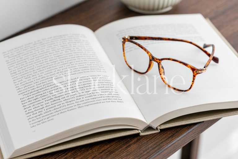 Horizontal stock photo of a book on a desk with a pair of glasses