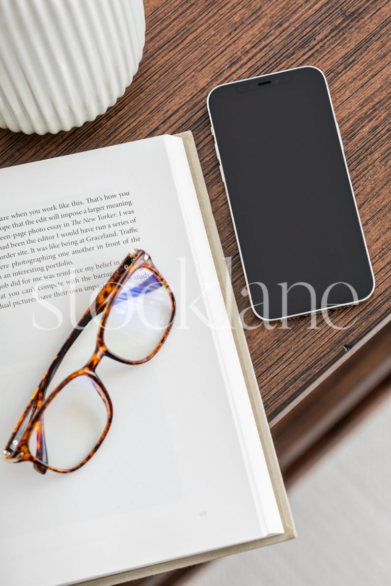Vertical stock photo of a desktop with a book and a phone