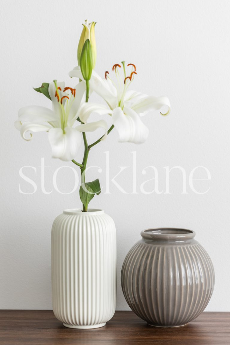 Vertical stock photo of white asian lilies with a white vase and a grey vase