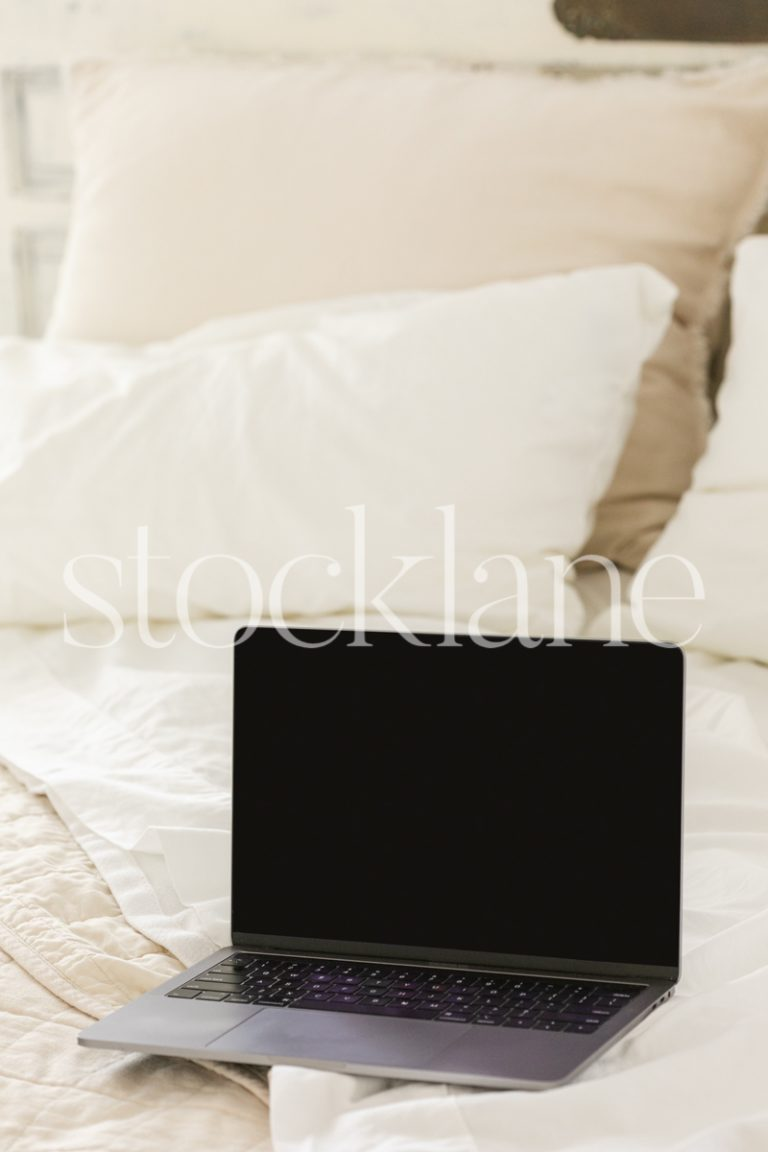 Vertical stock photo of a computer on a bed