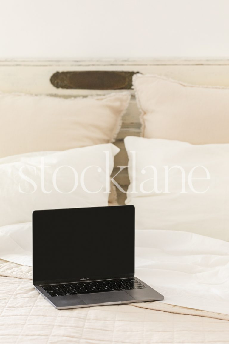Vertical stock photo a computer on a bed