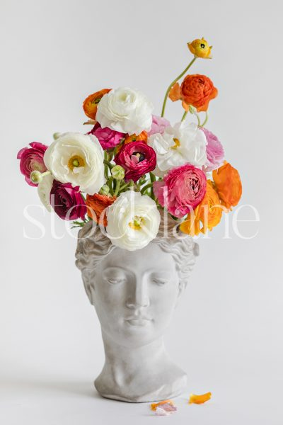 Vertical stock photo of a sculpture toped with colorful flowers.