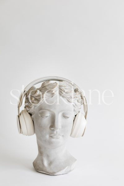 Vertical stock photo of a woman head sculpture with headphones