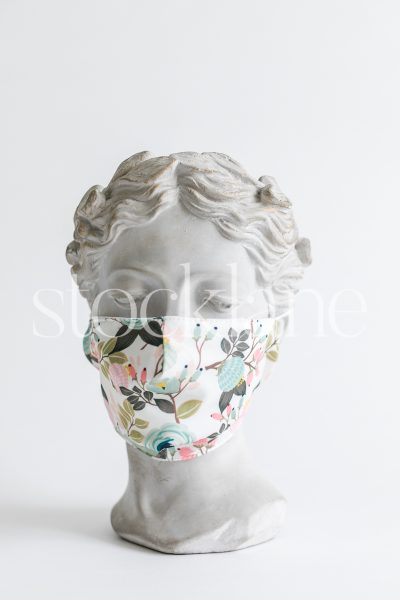 Vertical stock photo of a woman head sculpture with a floral mask.