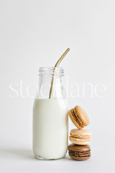 Vertical stock photo of a milk bottle and macarons.