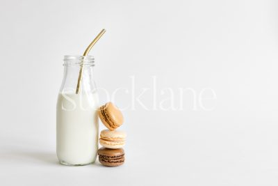 Horizontal stock photo of a milk bottle and macarons.