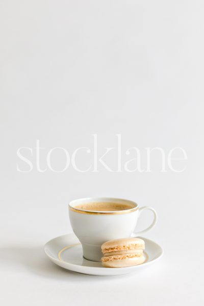 Vertical stock photo of a cup of coffee and a vanilla macaron.