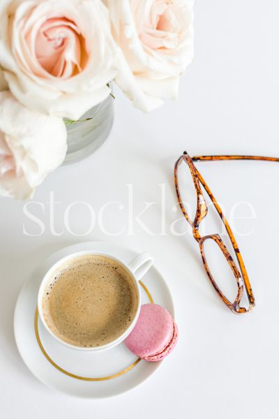 Vertical stock photo of a coffee cup with a pair of glasses and pink roses in the background.