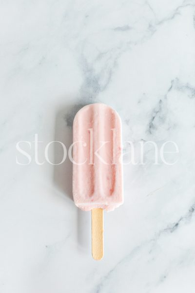 Vertical stock photo of a strawberry popsicle on a marble countertop.