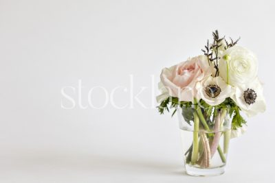 Horizontal stock photo of a flower bouquet with pink roses, white anemone and white ranunculus.