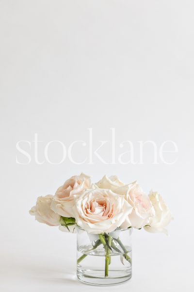 Vertical stock photo of a vase with pink roses.
