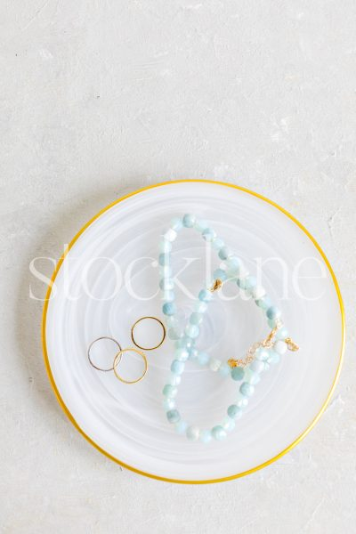 Vertical stock photo of a gold-rimmed plate with jewelry.