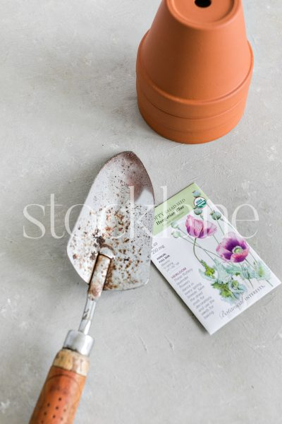 Vertical stock photo of flower pots, seeds and gardening tools.