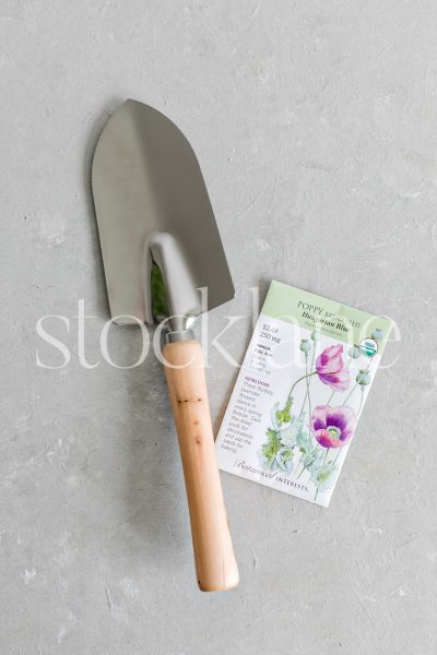 Vertical stock photo of a packet of seeds and a gardening tool.