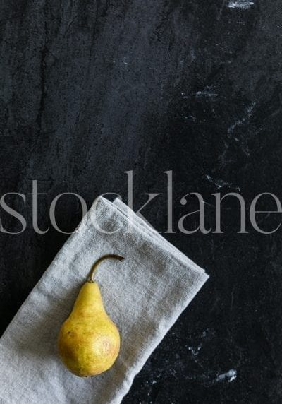 Vertical stock photo of pear in dark background