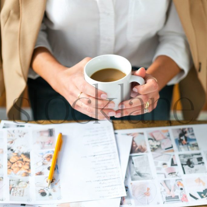 Vertical stock photo of woman with coffee cup working