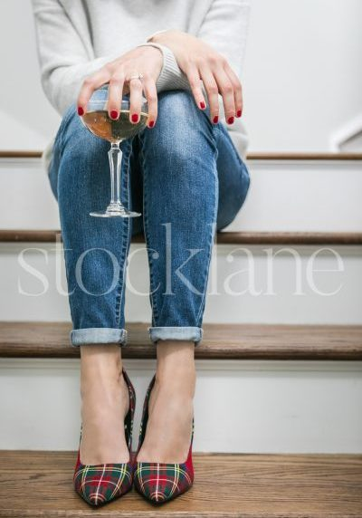 Vertical stock photo of woman sitting on steps with a glass of champagne